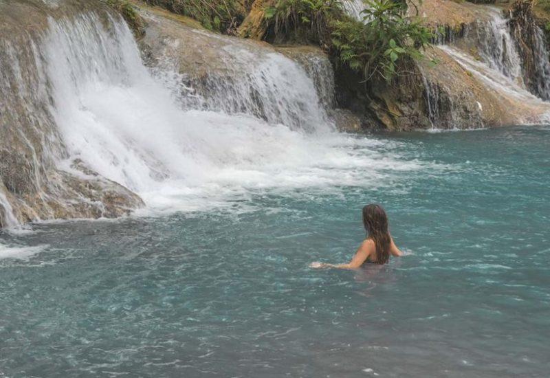 Jasmin steht im Wasser des Cambugahay Wasserfalls in Siquijor auf den Philippinen
