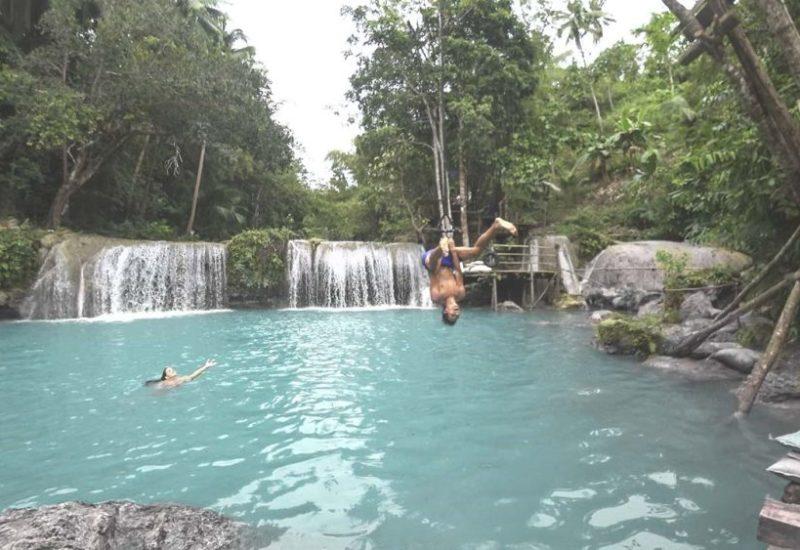 Valentin springt an einer Liane in den Cambugahay Wasserfall