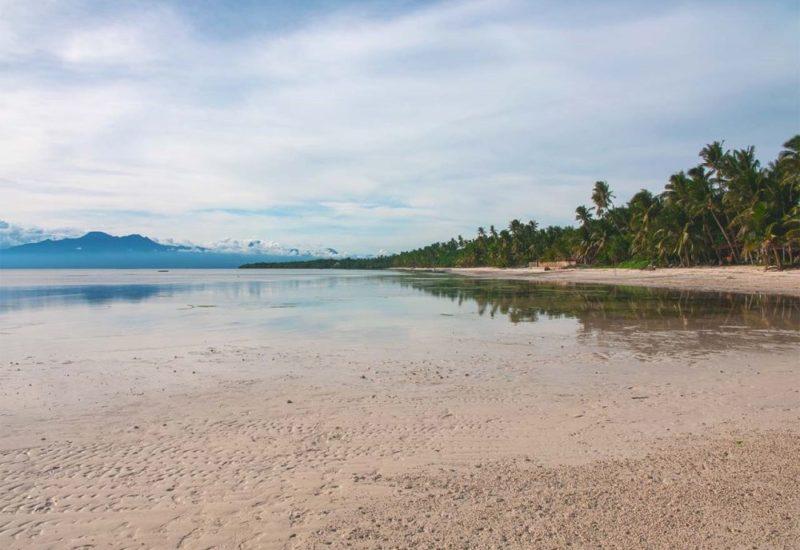 Reflexionen am Solangon Beach mit Bergen, Palmen und glasklarem Wasser