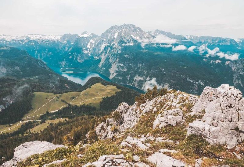 1000 Places to see before you die: Der Königssee in Bayern ist für uns einer der schönsten Orte weltweit. Das liegt vor allem an der unberührten Natur, den imposanten Berglandschaften, Wasserfällen und dem glasklaren Wasser im See.